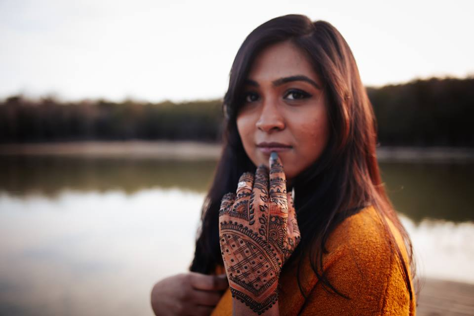 Vidhi looking at camera with henna on hand